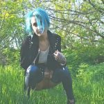 Blue haired alternative chick is  piss in forest.
